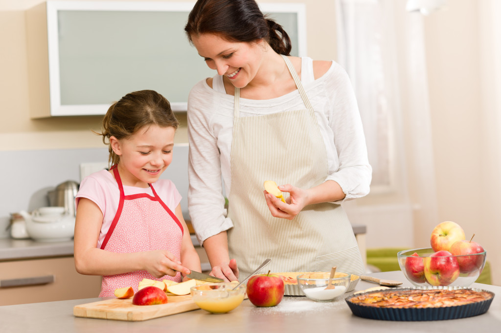 Mother and daughter cutting apples for pie
