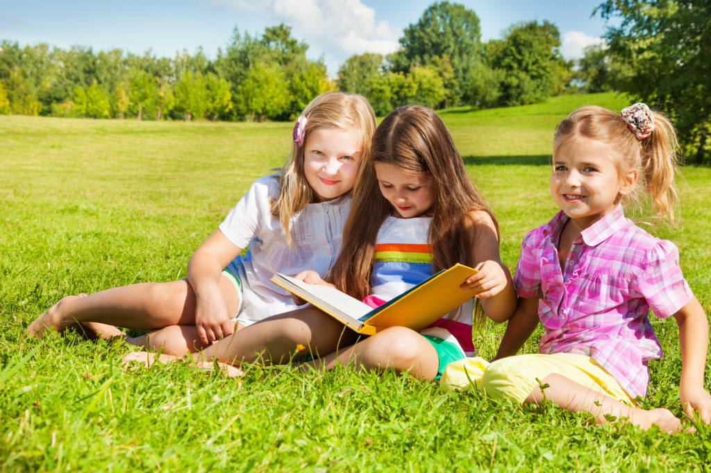 Three sisters read book in the park