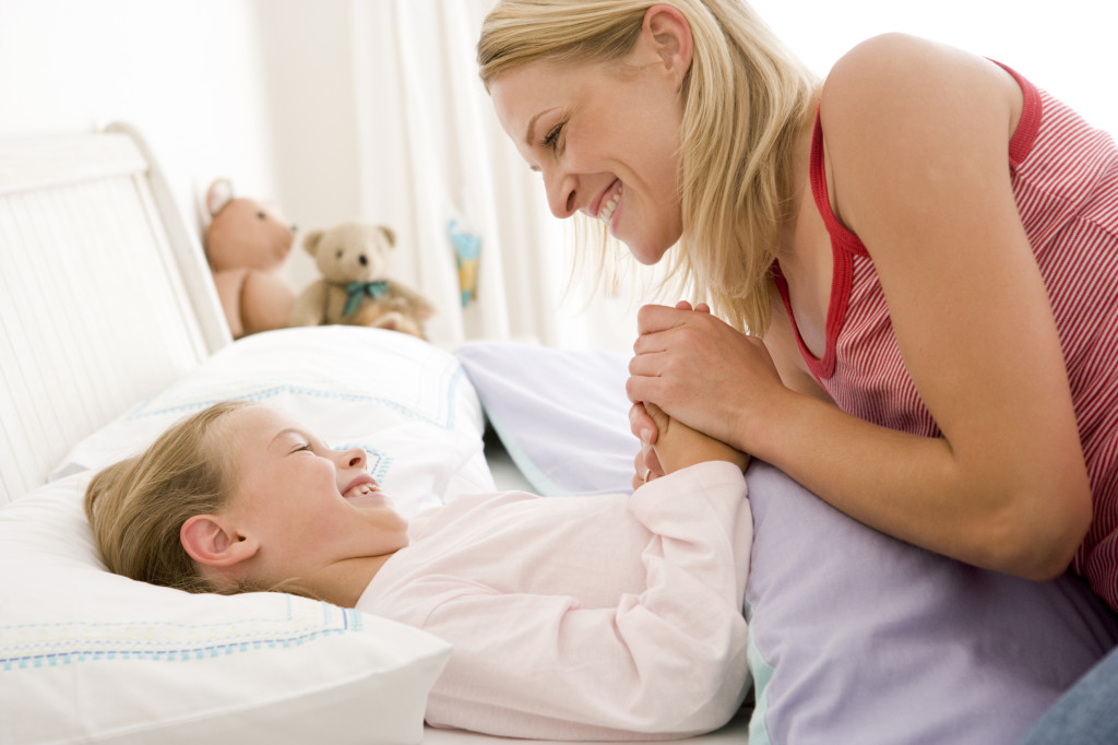 Woman with young girl in bed smiling